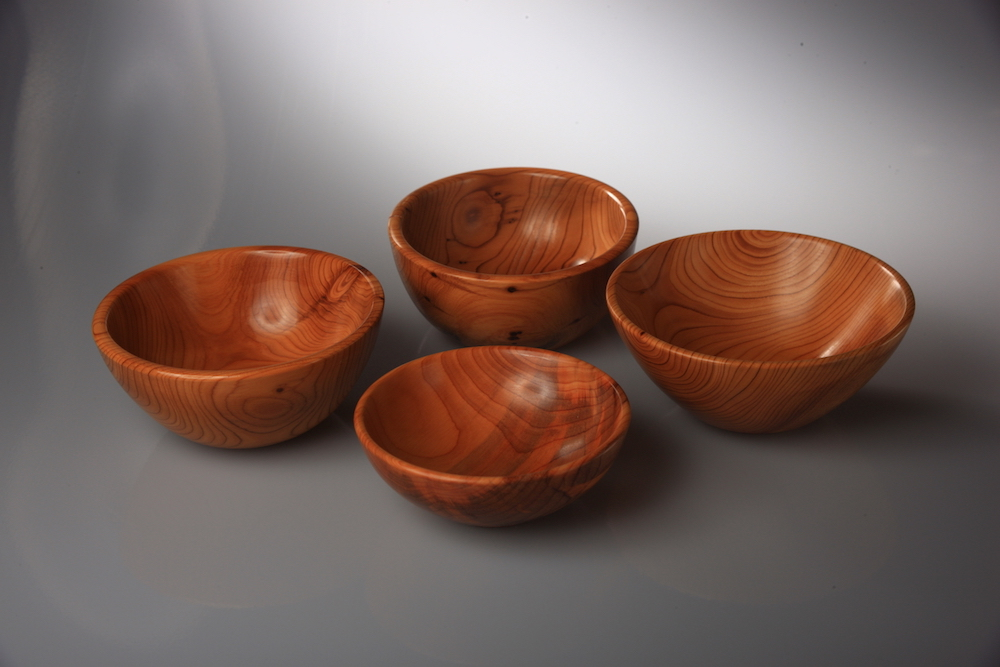 A group of four small bowls made in  			Yew.